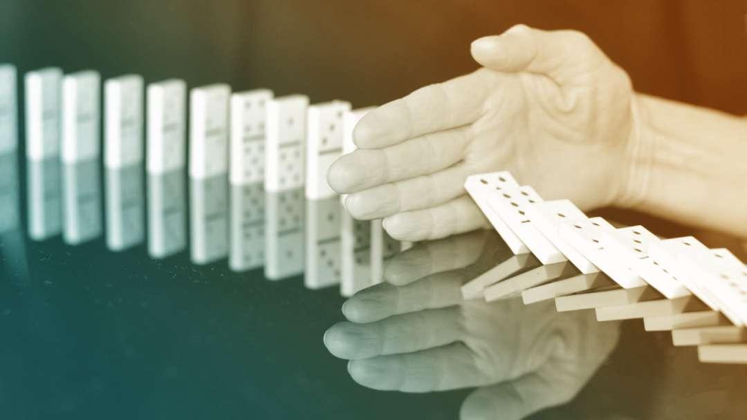 Main empêchant les dominos de tomber