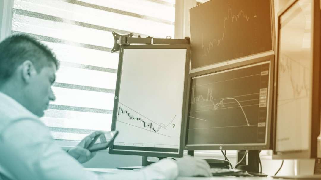 Trader en bourse avec plusieurs écrans