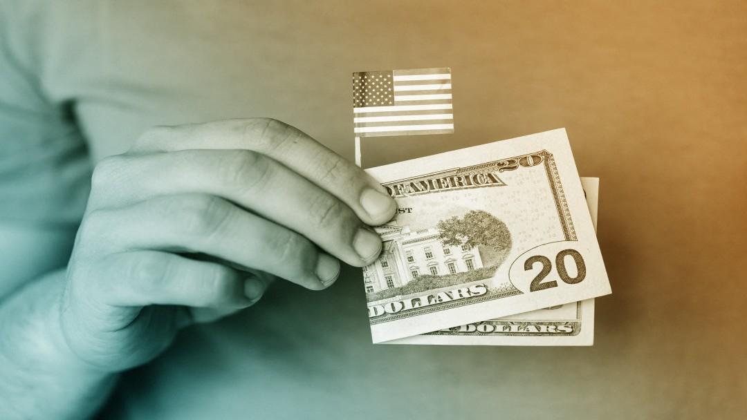 Homme tenant dans sa main un mini drapeau américain entouré d'un billet de 20 dollars