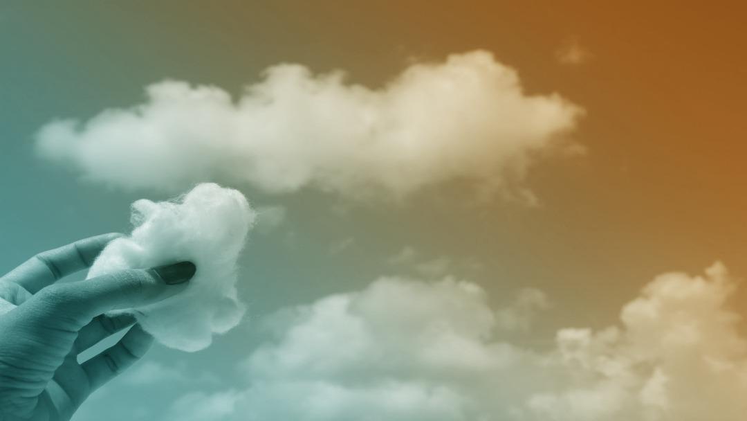 Nuage dans le ciel et mains tenant un morceau de coton en forme de nuage