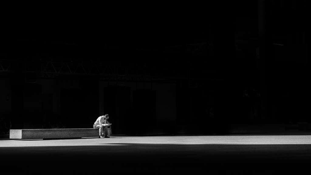 Homme seul sur un banc regardant son téléphone portable