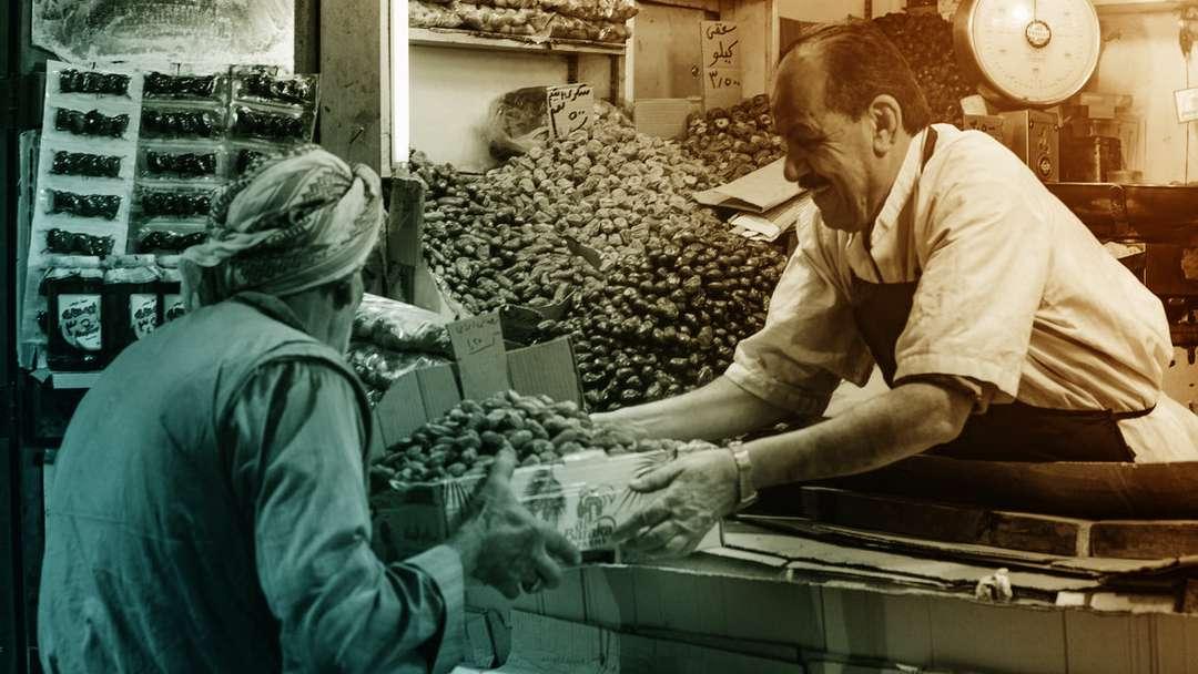 Un vendeur de dattes donne une caissette à un acheteur