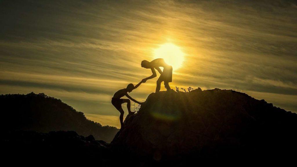 Une personne aidant un indivdu à grimper sur un sommet
