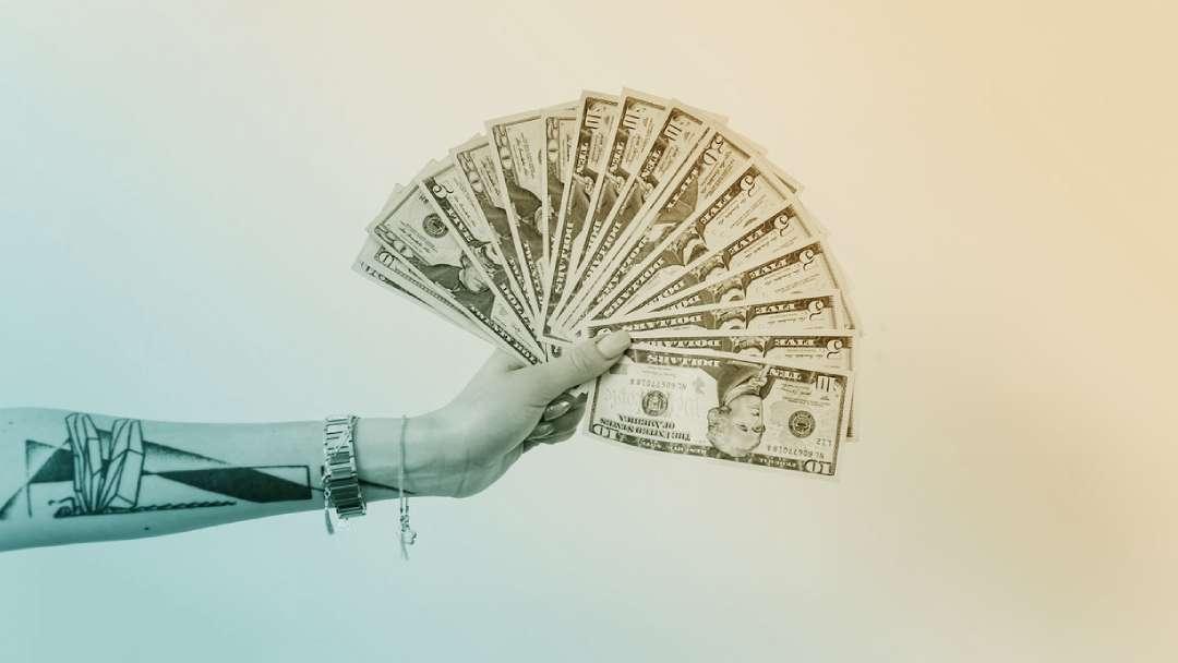 Main qui tient un liasse de billet en éventail