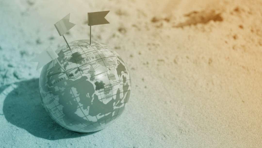 Globe terrestre avec trois petits drapeaux plantés dessus