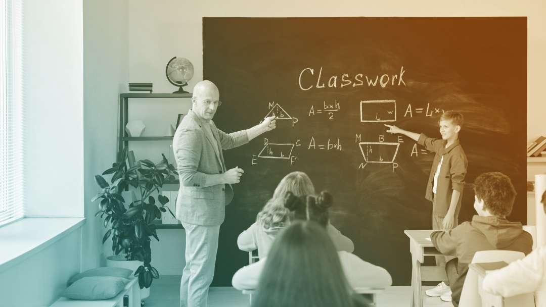 Professeur et élève qui pointent du doigt des figures géométriques au tableau