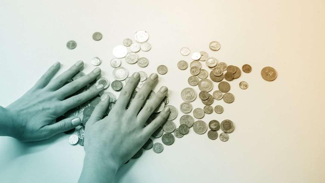Mains posées sur pièces de monnaies