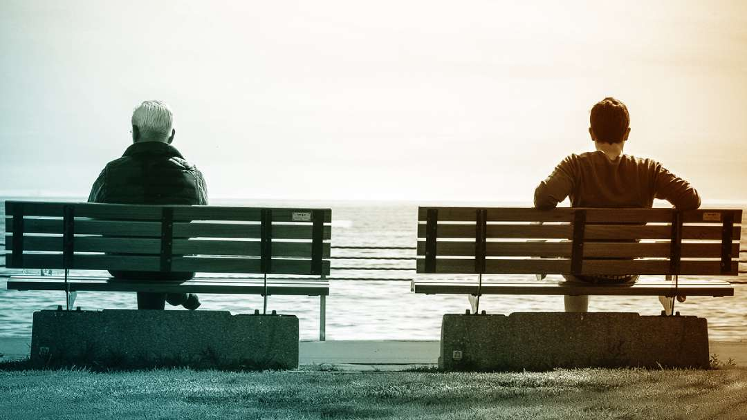 Un homme d'âge mûr et un jeune homme assis sur deux bancs séparés