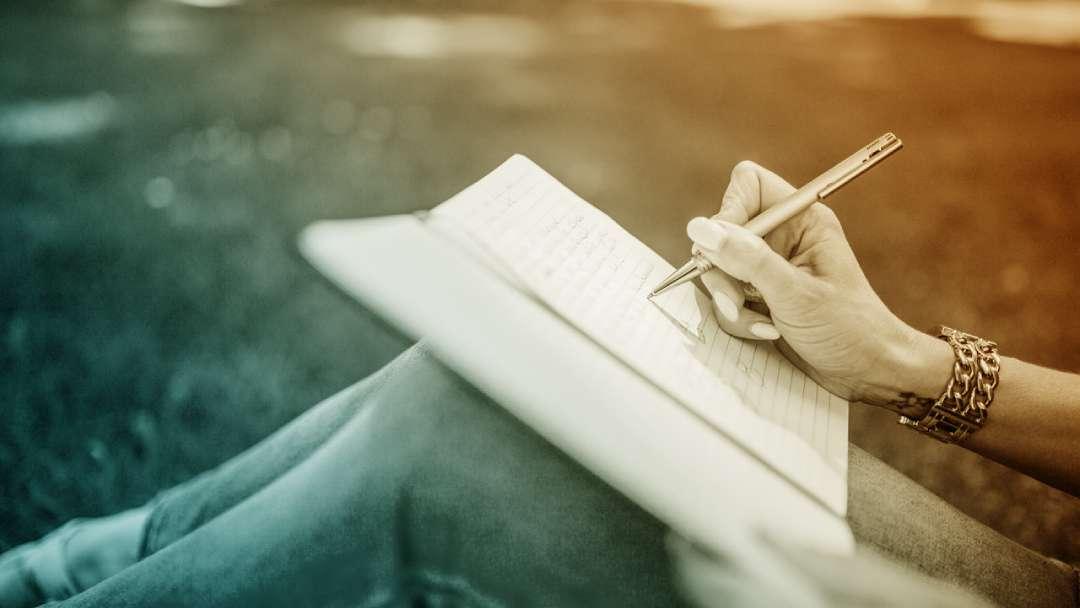 Main de femme qui écrit sur un cahier