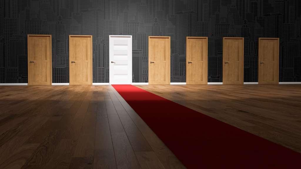 Sept portes dont une blanche mise en valeur par un tapis rouge