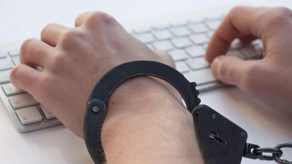 mains menottées tapant sur un clavier d'ordinateur