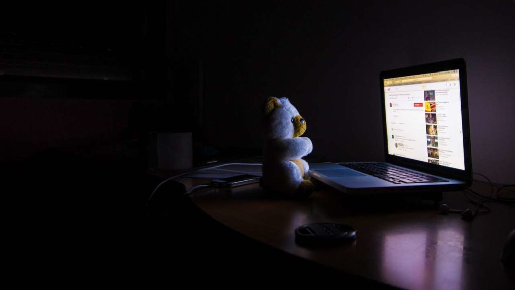 Ours en peluche dans le noir devant un écran d'ordinateur