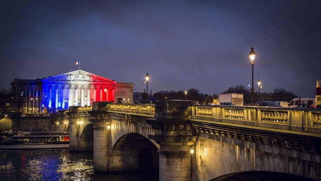 Vue panoramique du pont Alexandre III et de l'Assemblée Nationale parée d'un drapeau français