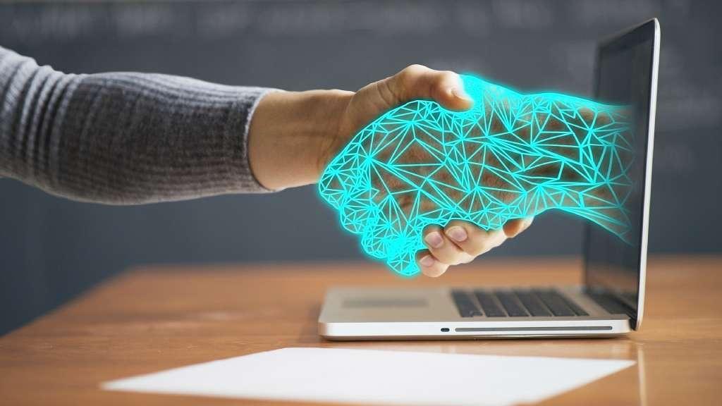Poignée de main humaine et digitale à travers l'écran d'un ordinateur