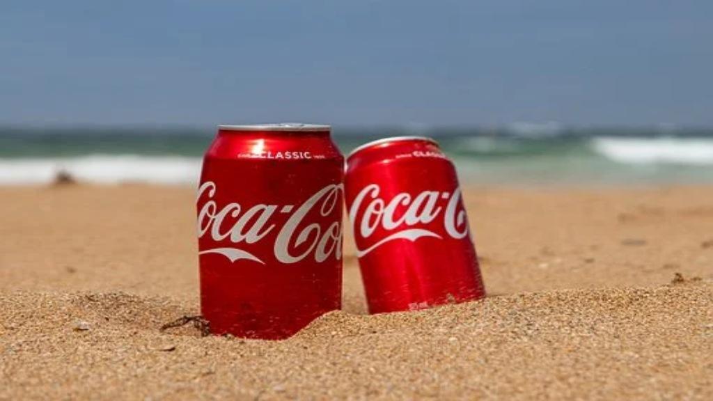 2 canettes de Coca Cola sur une plage