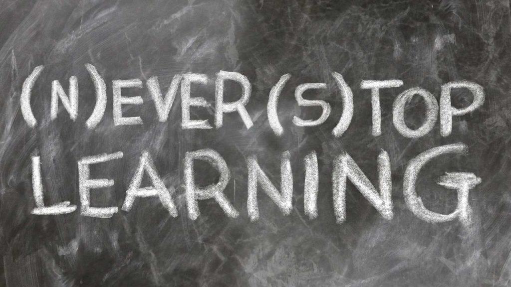 """Tableau noir avec l'inscription : """"ne jamais cesser d'apprendre"""" / ëtre au top de l'apprentissage"""