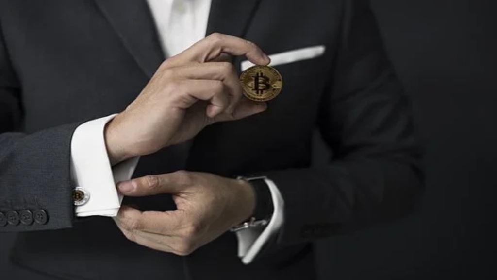 Homme en costume tenant un jeton de Bitcoin