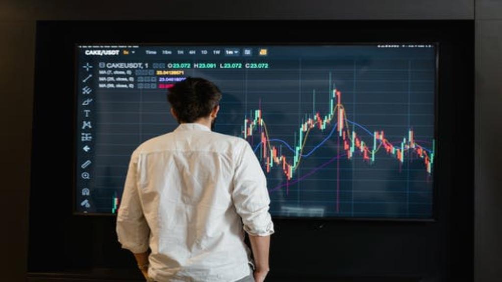 Un homme devant un grand écran de trading